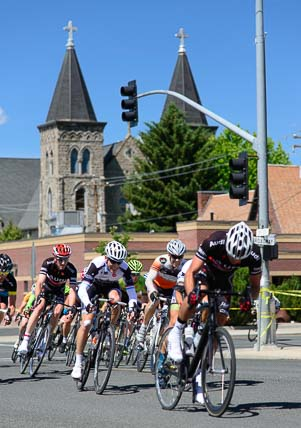 Bicycle racers pass Baker City Oregon's St. Francis Cathedral