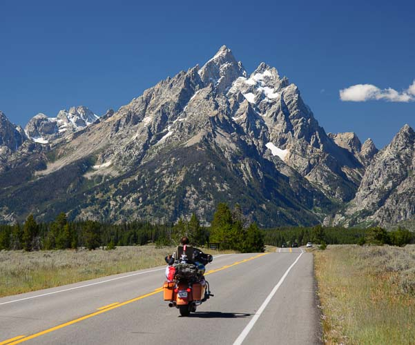 A motorcycle rides into Grand Teton NP Wyoming