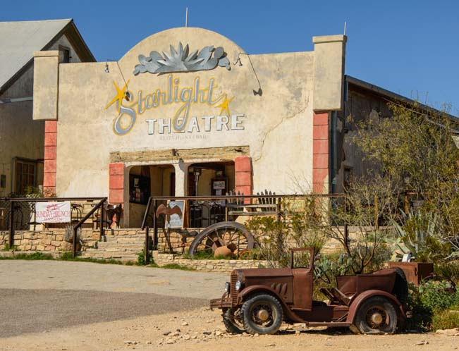 Rusty antique car and old theater building in Terlingua