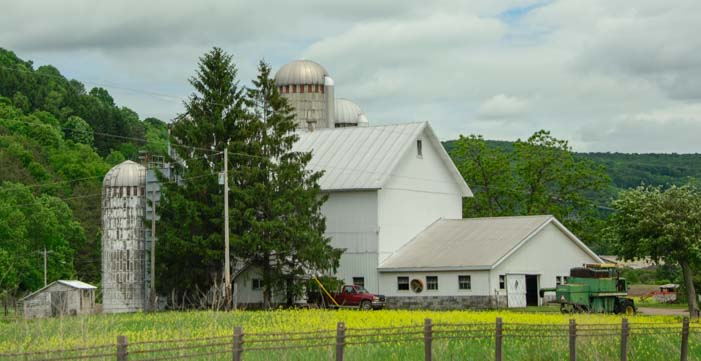 White farm with silo in New York Catkills Mountains in New York