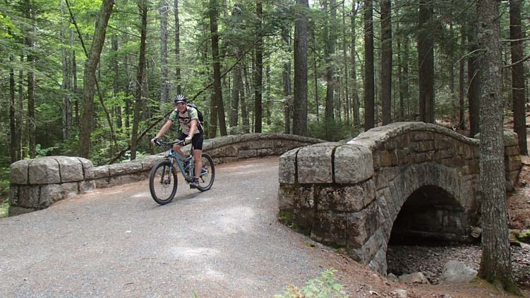 Bike riding over a carriage road bridge in Acadia National Park Maine