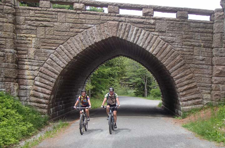 Bicycling carriage roads under a stone bridge at Acadia National Park Maine