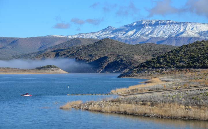 Boat on Roosevelt Lake Arizona Snow on Mountains