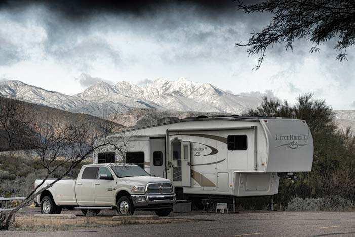 Fifth wheel trailer and Ram 3500 diesel dually truck at campground