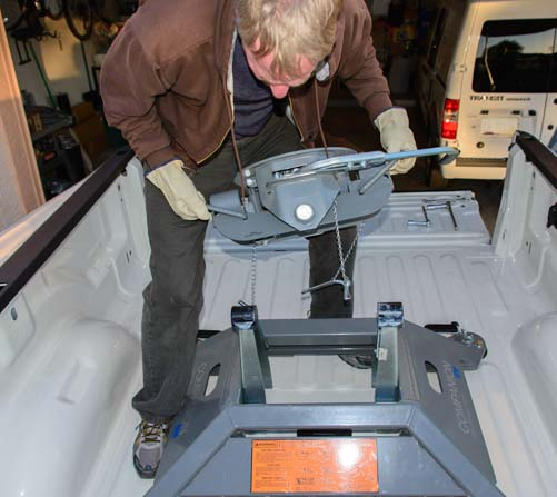 Placing fifth wheel hitch head on base in bed of truck