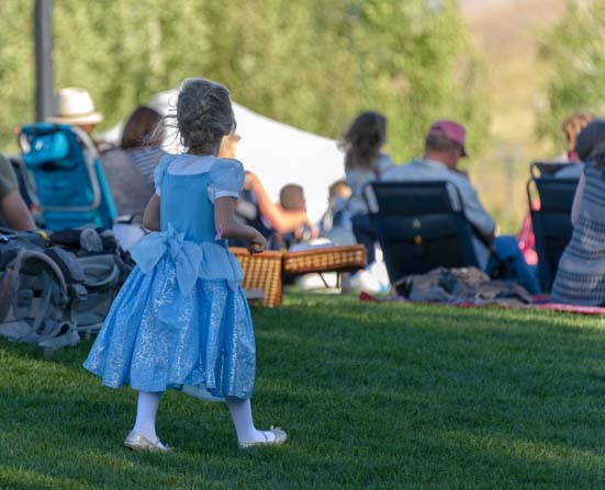 Little girl in party dress for Sun Valley Symphony summer concert on the lawn