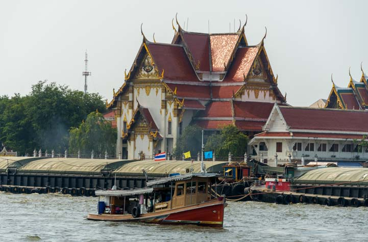 Boat and temple Chao Phraya River Bangkok Thailand