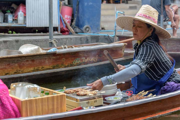Woman cooking in boat damnoen saduak floating market Bangkok Thailand