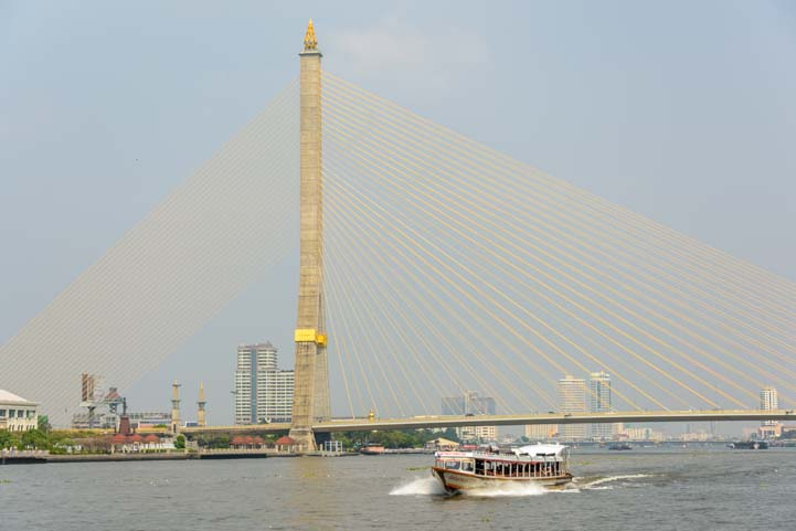 Boat and suspension bridge Chao Phraya River Bangkok Thailand