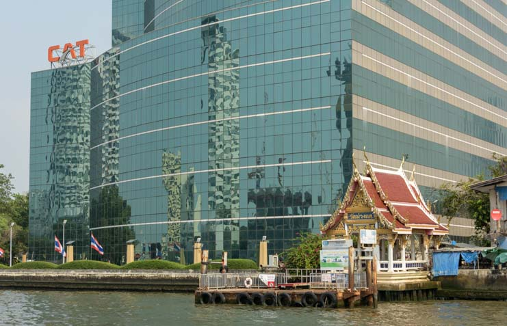 Temple and highrise building reflections Chao Phraya River Bangkok Thailand