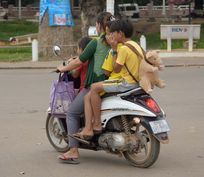 Family on motorbike with teddy bear Siem Reap Cambodia