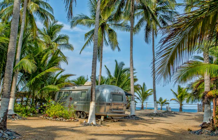 Airstream trailer in palm trees Mexico