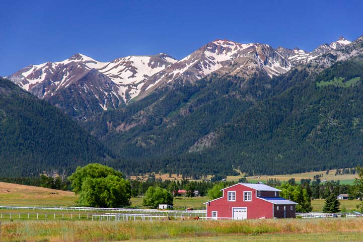 Snowcapped Wallowa Mountains Oregon with red barn