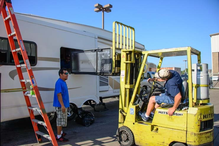 New RV refrigerator is fork lifter through the trailer window-min