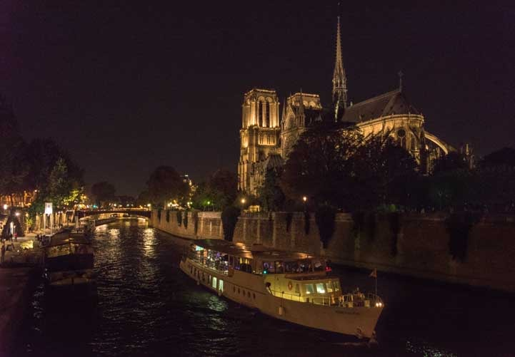 Notre Dame Cathedral and river boats on the Seine River Paris France-min