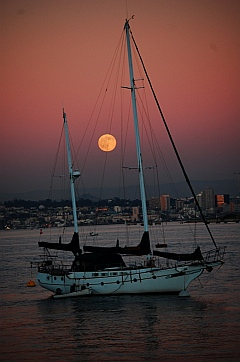 Full moon rises between the masts of a wooden schooner in San Diego