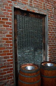 Empty liquor bottles form a window wall at Santo Tomas Winery
