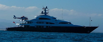 A megayacht too large for Marina Coral anchors outside.