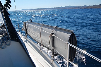 Porta-bote hull mounted on the lifelines of a sailboat