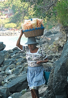 Vendors hike the rocks from La Ropa Beach to Las Gatas Beach, Zihuatanejo, Mexico.