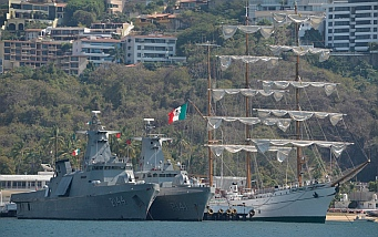 Navy warships and a tall ship in Acapulco Bay.