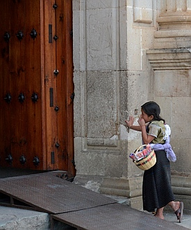 Young Chiclet seller gazes longingly at the wedding in the Santo Domingo Cathedral in Oaxaca, Mexico.