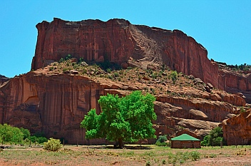 A hogan stands agains a dramatic backdrop of cliff walls on the lush valley floor of Chelly National Park, Arizona.