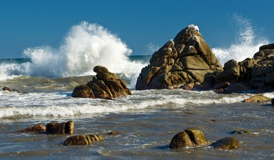 Rocks and crashing surf at Playa La Bocana Huatulco as seen while sailing Mexico