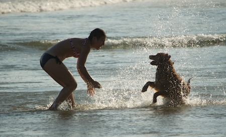 Girl playing with her dog at Playa La Bocana Beach in Huatulco