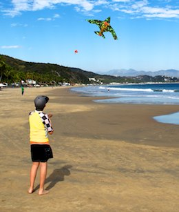 kid flies a kite on Santiago Beach