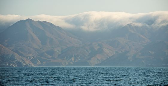 Swirling clouds, haze and towering mountains greet us as we approach Bahia Santa Maria.
