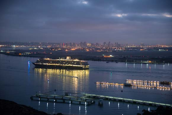 A cruise ship lights up the bay as it sails towards downtown
