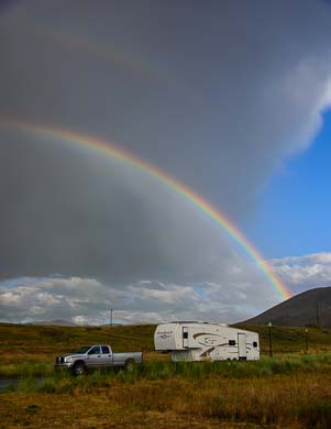 Fifth wheel trailer under a rainbow