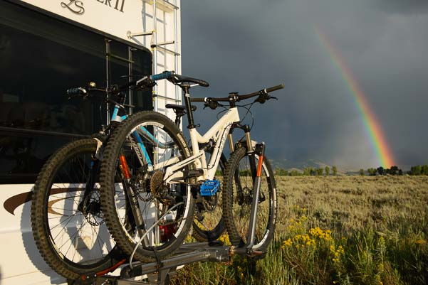 Fifth wheel RV with bikes and a rainbow