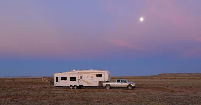 Fifth wheel RV at sunset with full moon