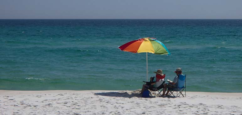 Couple with beach umbrella on Gulf of Mexico Florida