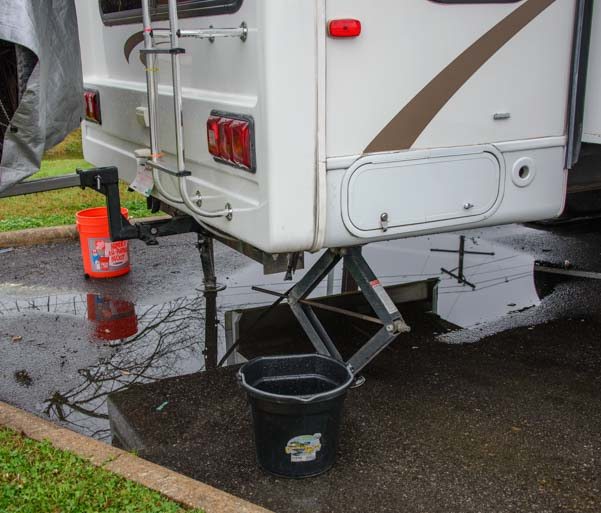 Buckets catch rain from the RV roof