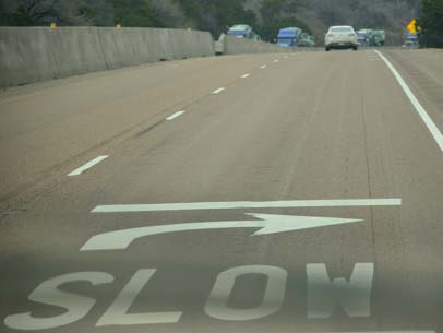 Slow sign painted on the pavement of I-20 in Texas