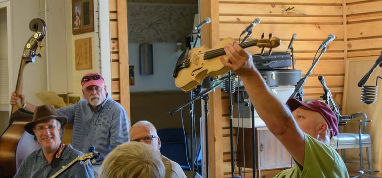 Holding up a fiddle at a bluegrass jam session in Floyd Virginia