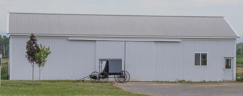 Amish buggy parked in front of barn