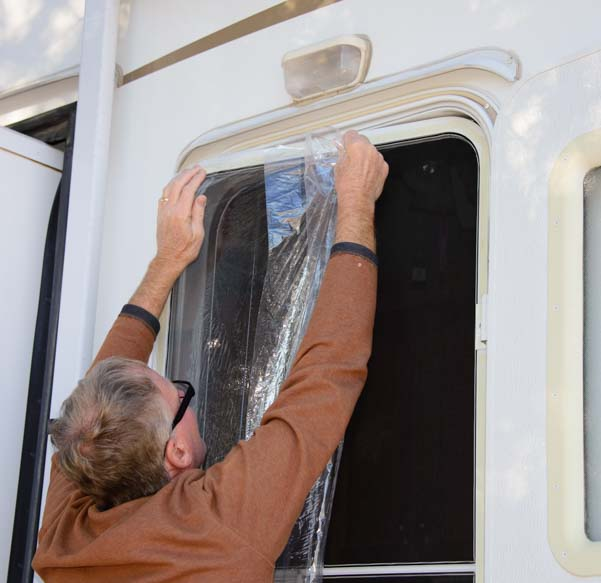 Winter RV Tips - Winterize screen door and hang plastic shrink film