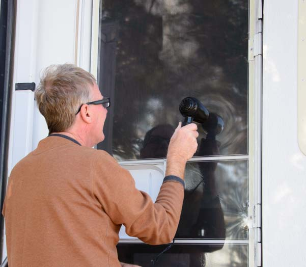 Shrink-wrap RV screen door and shrink plastic film with hair dryer