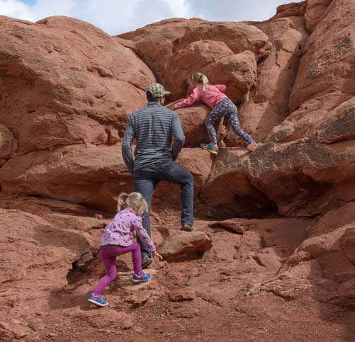 Kids climbing on rocks Arches National Park Utah