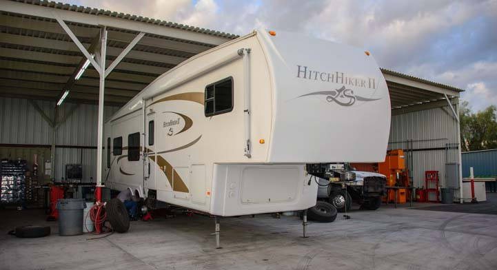 Fifth wheel trailer RV at suspension shop for service