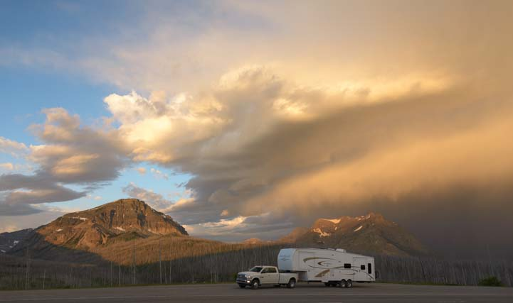 RV in dawn stormy skies Glacier National Park Montana