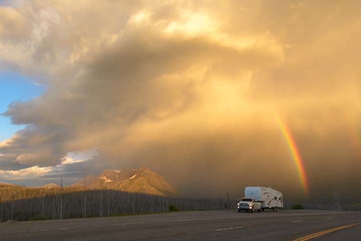 RV in rainbow stormy skies Glacier National Park Montana