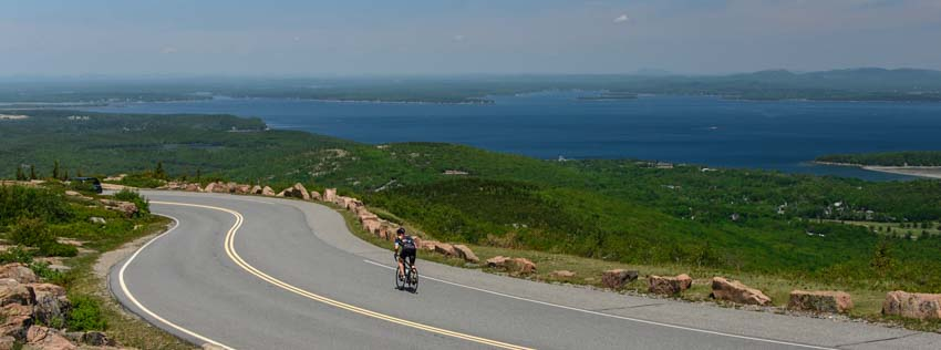 Cyclist rides down Cadillac Mountain Acadia National Park Maine