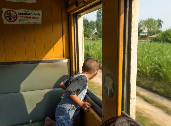 Looking out train window Train from Bangkok to Kanchanaburi Thailand