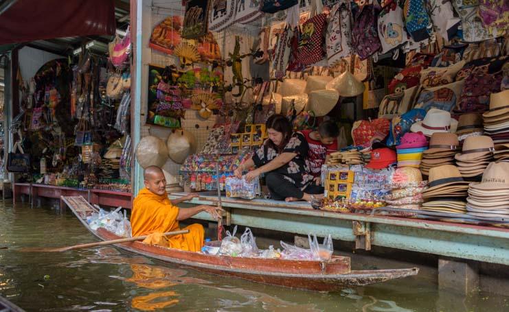 Buddhist monk shopping Damnoen saduak floating market Bangkok Thailand