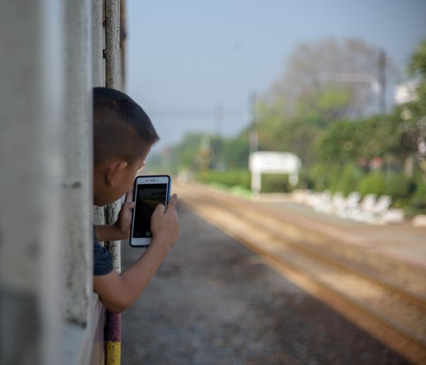 Boy with cell phone on Kanchanaburi train